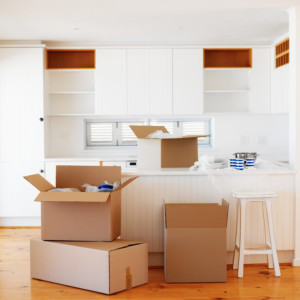 Open cardboard boxes kept in an empty kitchen